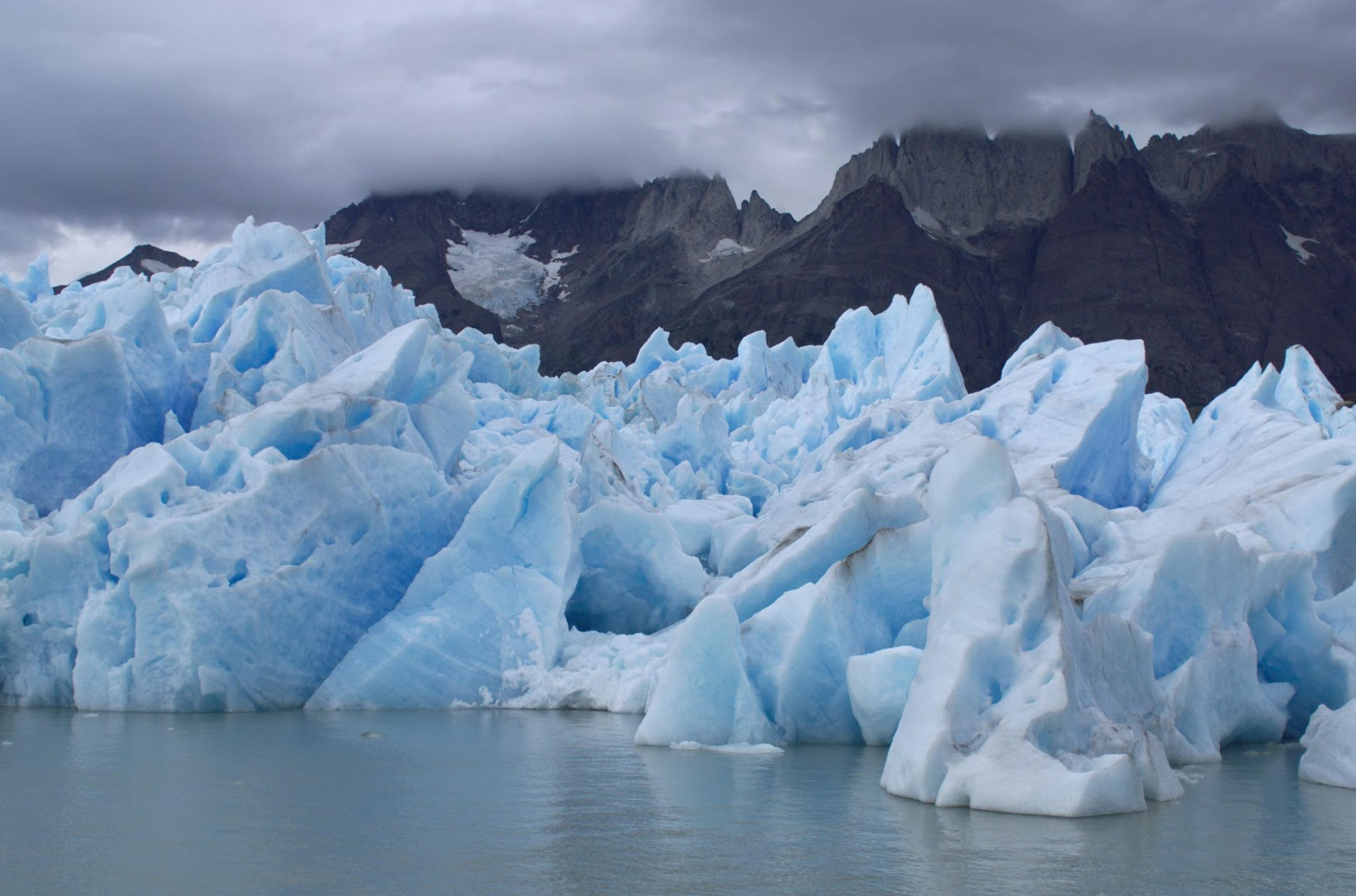 Photo of glacier ice in ocean with land in the background