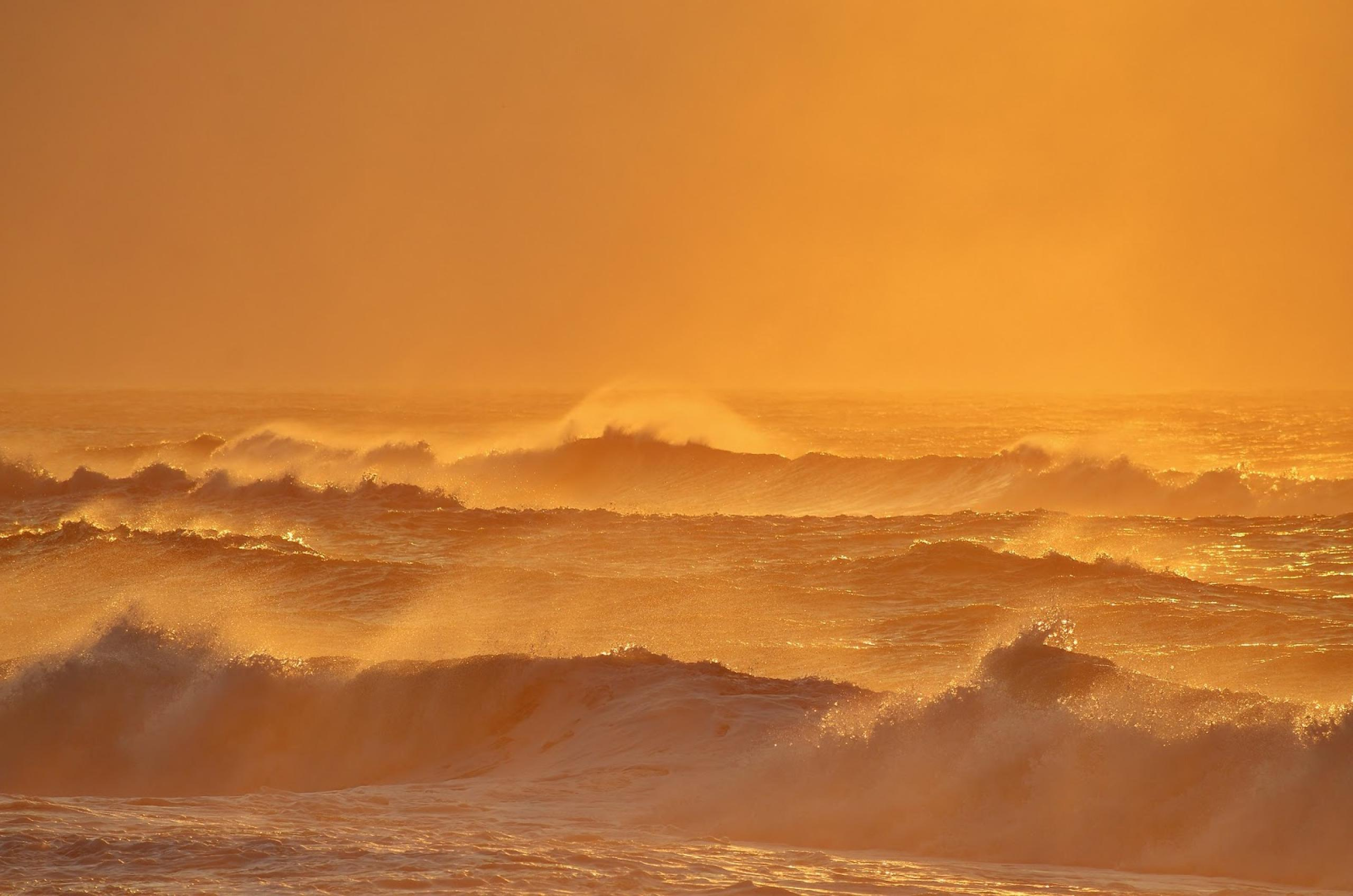 Photo of large ocean waves with an orange hazy sky
