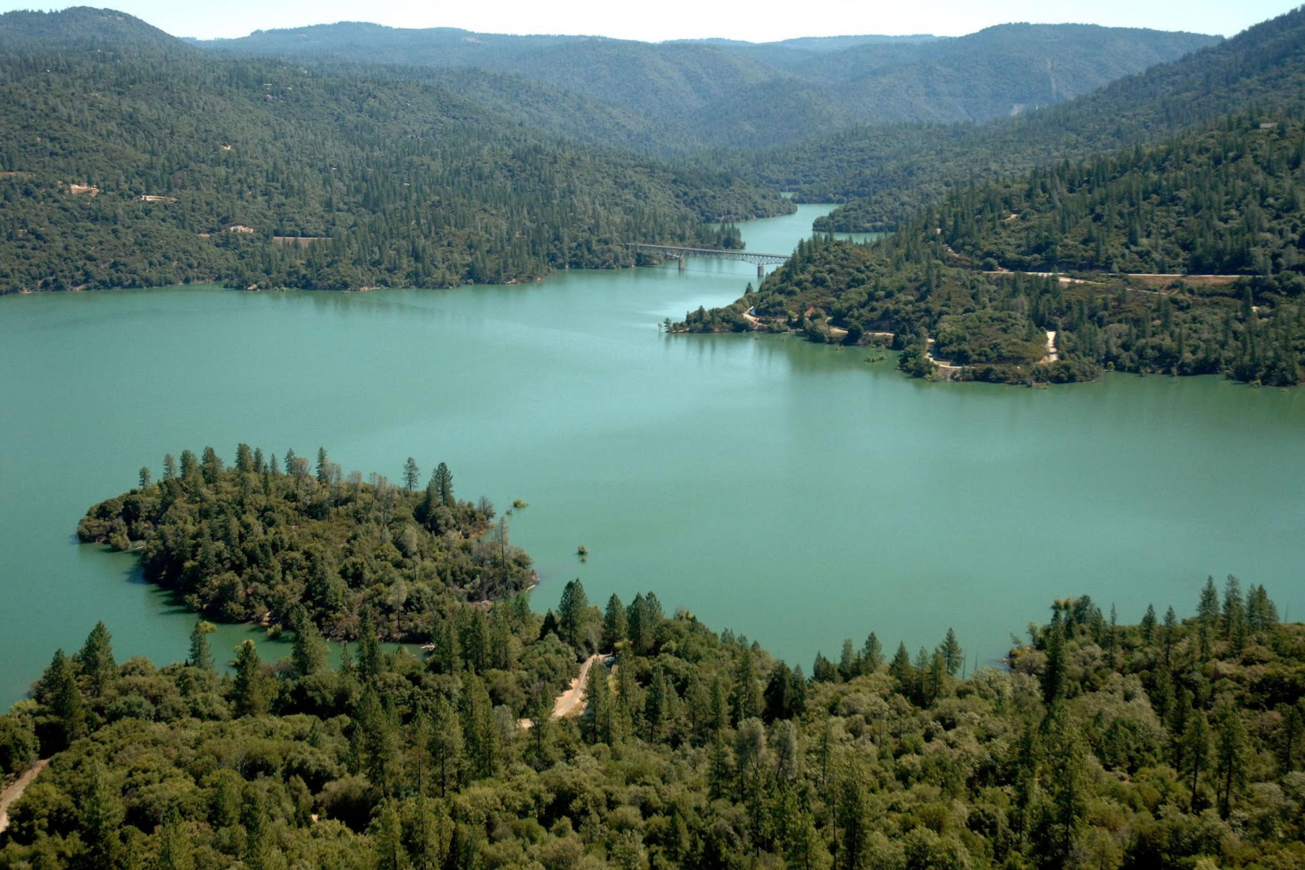 Photo of lake with wooded land surrounding it