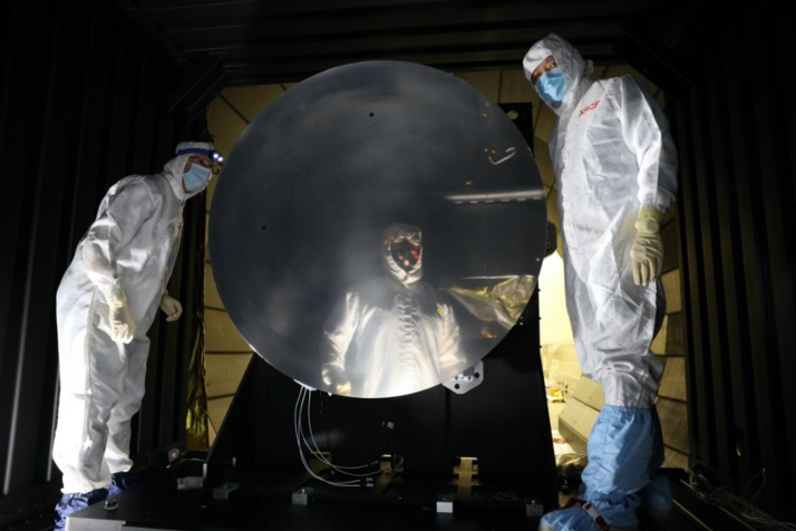 Photo of two male scientists in lab suits next to a large scale mirror and one scientist reflected in the mirror.