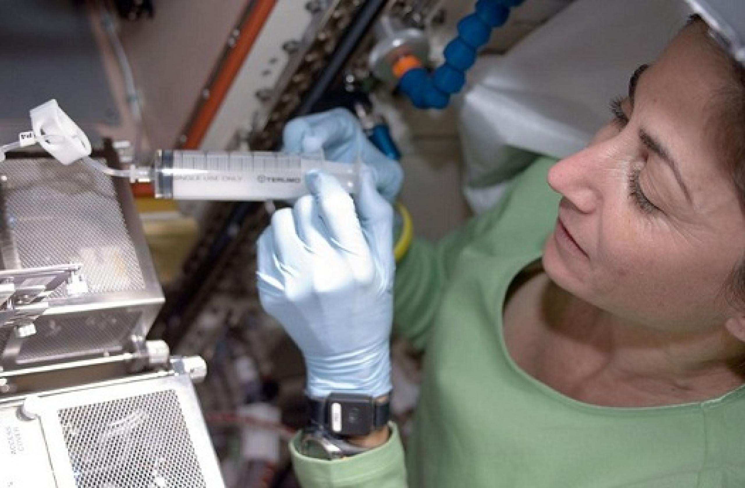 Woman in laboratory holding syringe connected to metallic equipment.