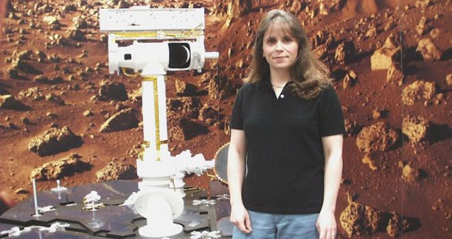 Ashley Stroupe stands next to a model of the Mars Exploration Rover she drove on Mars.