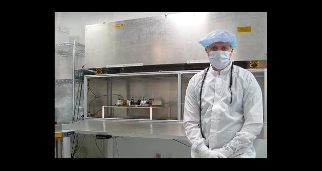 Photo of man standing in science lab wearing protective clothing.