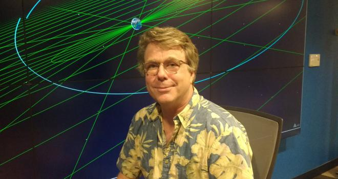 Roland Vanderspek seated in front of a projector screen.