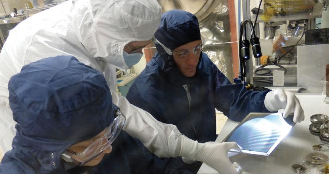 Scientists in lab inspecting a sensor plate