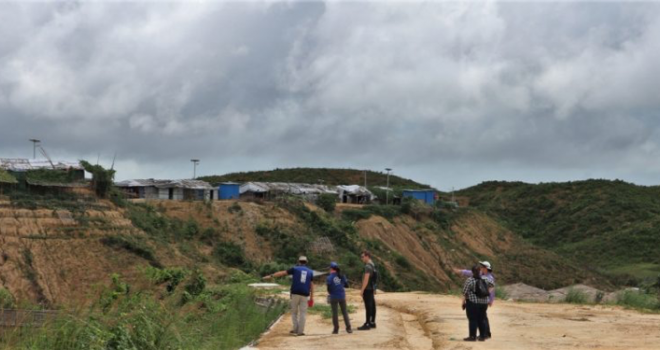 Photo of scientists reviewing landscape in Rohingya