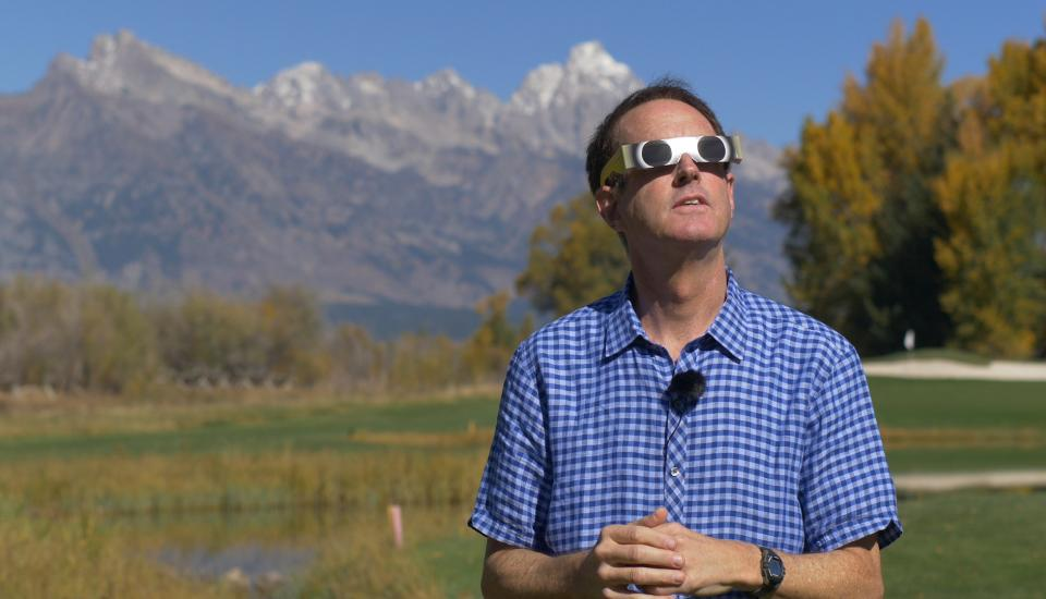 Photo of man wearing special glasses for sky watching with mountains in the background