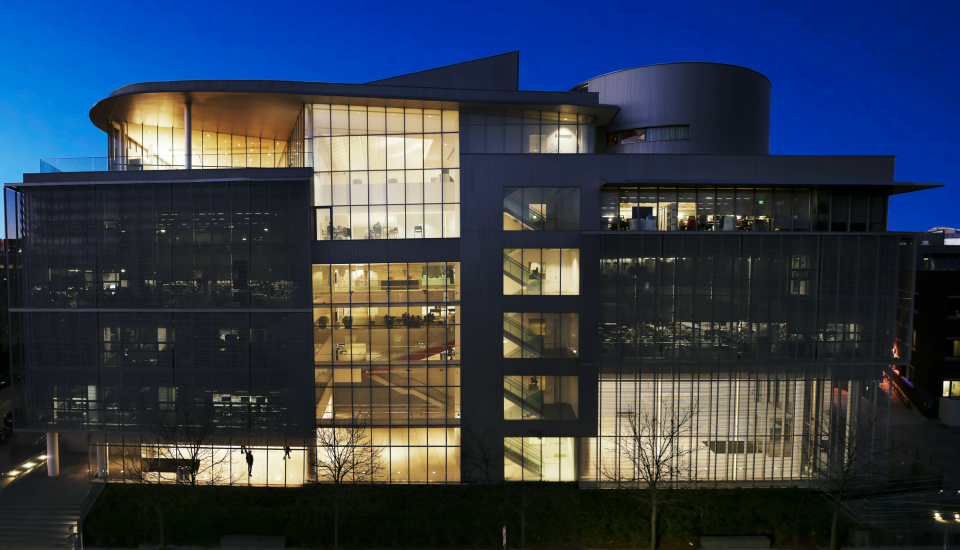 Photo of large 6-story modern academic building at night with lights illuminating the interior