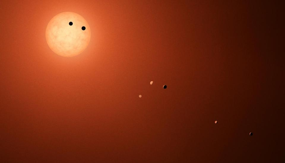illustration shows the seven TRAPPIST-1 planets as they might look as viewed from Earth using a fictional, incredibly powerful telescope