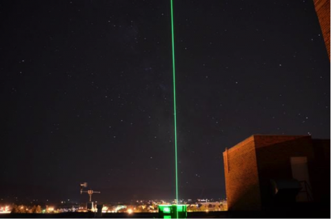 Two lidar beams look up into the sky from the roof of the optical remote sensing laboratory at Montana State University in Bozeman, Montana, USA. The visible green laser beam is measuring the atmospheric profile of aerosols and clouds, while the invisible infrared laser beam is measuring water vapor. The lidars are in a laboratory on the top floor of the engineering building and transmit to the atmosphere through a roof port hatch. Credit: NASA/A. Nehrir.