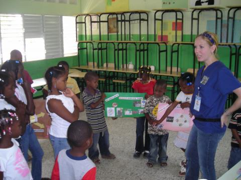 Photo of Helena Chapman teaching children in the Dominican Republic about diseases