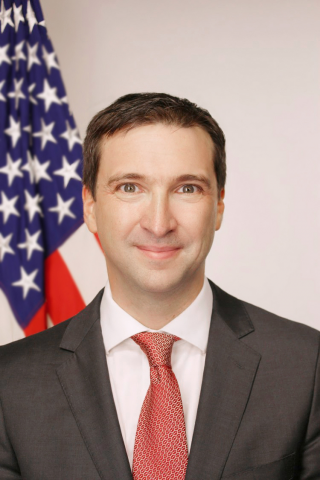 Portrait photo of a man wearing a suit and tie in front of the American Flag