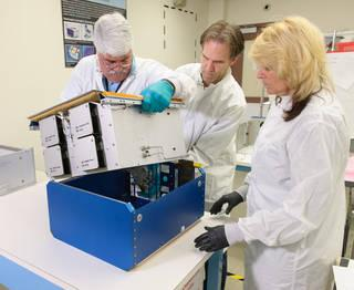 Two male and one female scientist assembled removing a white piece of equipment from a blue casing.