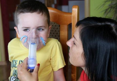 Child being administered an inhaler by woman