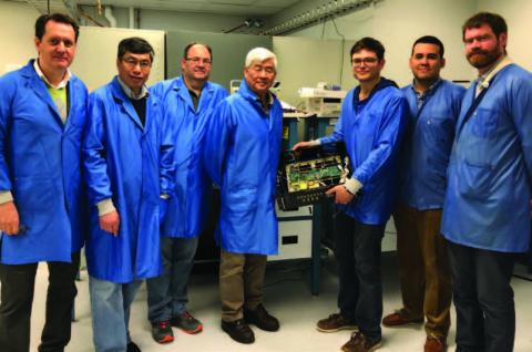 Photo of team of scientists in blue lab jackets