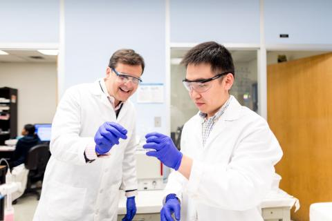 2)Two men wearing lab coats, protective eyewear, and surgical gloves each hold one end of a long, slender tube.