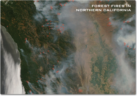 A satellite image showing smoke from forest fires wisping across the forest covered landscape of Northern California. Bright red areas at the base of these smoke plumes indicates the size of the actual area on fire.