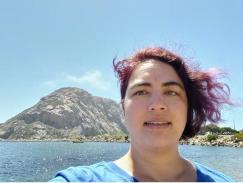 Photo of woman with water and rock formation in the background.