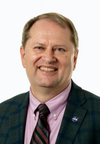 A formal portrait of a smiling caucasian male with blond hair and blue eyes. He is wearing a pink shirt with a striped tie and a dark suit. A NASA lapel is located on his left lapel.