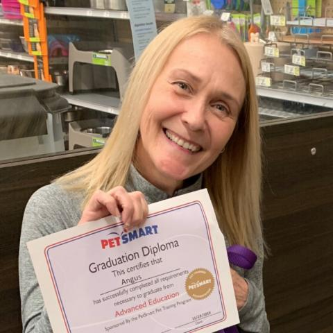 Melissa A. Morris holding a PetSmart graduation diploma.