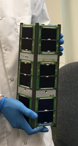 Photo of hands in blue latex gloves holding the Q-PACE satellite, a small device