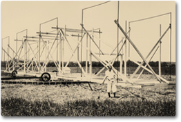 An old photograph of Karl Jansky standing in front of his radio telescope.