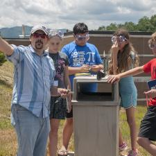 Photo of instructor and students doing a science project outside