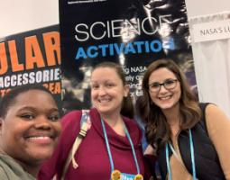 Three people posing in front of a Science Activation booth.