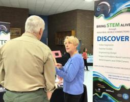 Sharon Bowers talks to a man at the eClips exhibit booth.
