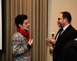 Dr. Jonathan Lunine converses with a man in a red scarf.