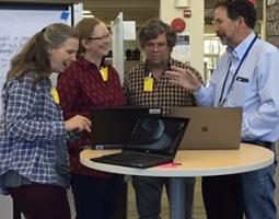 Four people chatting around a table with three laptops