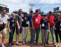 Nine people pose on a baseball field.