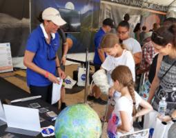 A young girl has her hand in a spacesuit glove at an Apollo booth.
