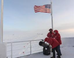 Three people in orange parkas with a telescope at the South Pole.