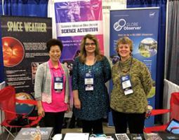 Carolyn Ng, Tina Harte, and Christine Shupla pose at a NASA Science Activation booth.