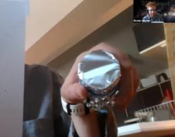 A hand holding a tinfoil-wrapped tube up to a webcam.
