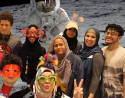 Eight people pose in front of a moon and astronaut backdrop.