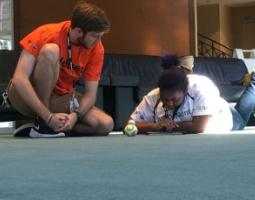 Two students on the floor with a BB-8 robot.
