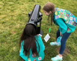 Two girl scouts use a telescope outside.