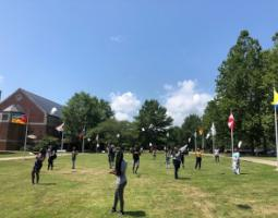 College students flying kites on a lawn.