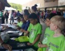 Children in lime green t-shirts at display tables.