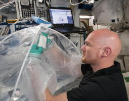 Photo of male astronaut wearing green latex gloves and handling an experiment underneath a clear plastic tent.