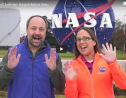 A man and woman holding their hands up in front of the NASA Langley meatball sculpture