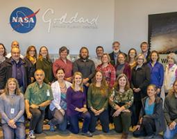Group photo in front of wall with NASA Goddard signage