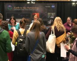 A group of people gathered in front of the Earth to Sky Partnership booth.