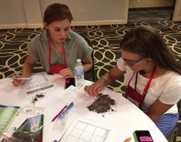 Two women observe a soil sample
