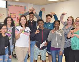 Students and teachers pose using sign language.