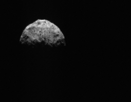 ghostly gray image of asteroid Bennu against black backdrop of space