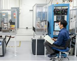 Photograph of two men wearing breathing masks and sitting in a lab with blue metal cases holding computer equipment.