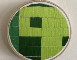 Photo of embroidered art, a green image representing a Landsat satellite image of earth